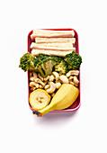 Lunchbox mit gesunder Mahlzeit aus Sandwich, Broccoli, Cashewnüssen und Banane