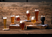 Various glasses of beer against a wooden background