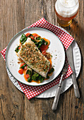 Wolf-fish fillet with a crispy garlic and herb crust on a bed of spinach