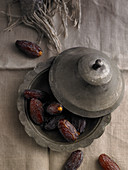 Pitted dates in a pewter container