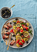 Potato salad with roasted vegetables and skewers with bacon