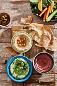 Red, green and yellow hummus with flatbread