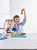 Kinder essen knusprige Hähnchenstreifen mit Ketchup
