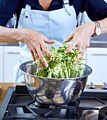 Zucchini mit den Händen vermischen