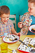Kinder essen ofengebackene Heidelbeer-Orangen-Pancakes