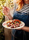 Frau isst Lamm und Kürbis vom Holzkohlegrill