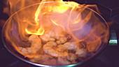 Garnelen mit Knoblauch in einer Pfanne mit brennender Flamme zubereiten