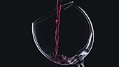 Rotwein im Weinglas vor schwarzem Hintergrund