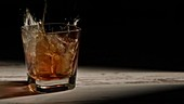 Person pouring ice cubes into glass with bourbon on wooden table in rays against black background