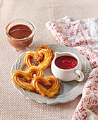 Heart-shaped churros with raspberry and chocolate sauce