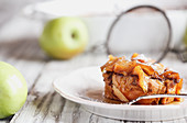 Apple French toast casserole with maple syrup and powdered sugar