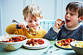 Boys eating slow cooker sausage casserole
