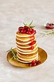 Ein Stapel Pancakes mit Canberrysauce auf goldenem Teller