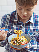 Boy eating noodle stir-fry with crunchy peanuts