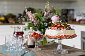 Strawberry cake and crystal glasses on rustic wooden table