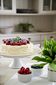 Cake topped with berries and posy of lily-of-the-valley on dining table