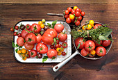 Different types of tomatoes in vintage containers