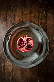 Half pomegranate on a metal plate