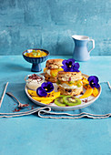 Cranberry scones with mango and kiwi cream and edible flowers