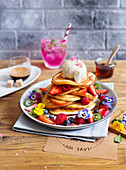 Fluffy pancakes with fresh berries, ice cream and edible flowers