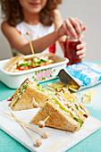 Mädchen isst Clubsandwich mit Ei und Kresse