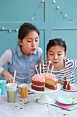 Zwei Mädchen pusten die Kerzen auf einer Geburtstagstorte aus