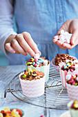 Schokoladenküchlein mit Marshmallows, Smarties und Trockenfrüchten verzieren