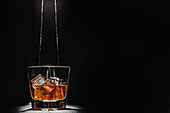 Person filling transparent glass with bourbon on wooden table in rays against black background