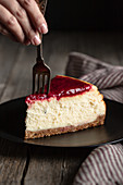 Crop female with fork eating delicious homemade cheesecake with red berry jam served on black plate on wooden table