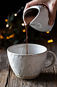 Crop woman pouring delicious hot chocolate into elegant white cup placed on wooden table