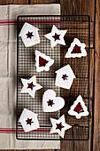 Verschieden geformte Kekse mit roter Beerenmarmelade und Puderzucker zu Weihnachten