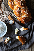 Fresh appetizing braided round bread with sprinkles on metal grid on table with Christmas decorative elements