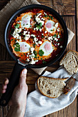Frying pan with delicious shakshuka made with fried eggs with vegetables and feta cheese