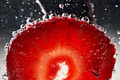Closeup ripe red sliced strawberry covered with air bubbles floating in transparent clear water