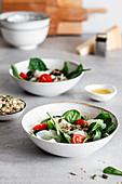 Fischsalat mit Spinat, gehackten Kirschtomaten und schwarzen Oliven