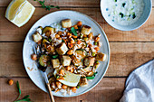 Healthy salad with rice and grilled tofu and vegetables served in bowl on wooden table