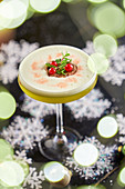 Round glass of mezcal cocktail with kiwi and maple syrup with table decorated with snow stars