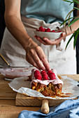 Crop anonymous female with homemade cake with glaze and fresh raspberries in home kitchen
