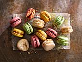 Verschiedene bunte Macarons auf Papier und Holzuntergrund