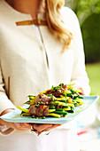 Woman serving prosciutto-wrapped bean bundles