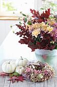 Strauß aus Chrysanthemen mit Herbstlaub, weiße Kürbisse mit Kranz aus Hortensienblüten und rosa Pfeffer, Blätter vom Amberbaum