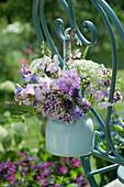 Kleiner Strauß aus Wicken, Flockenblume, Oregano, Glockenblumen und Wiesenkümmel an Stuhllehne gehängt