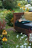 Sofa im Garten zum draußen wohnen im Sommer, umgeben von Sonnenhut, Strauchhortensien und Gräsern