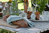 Frisches Chiabatta auf Holzbrett, Tablett mit Gemüsechips in Gläsern