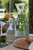 Glaskaraffe mit Wasser und Minze, Flasche mit Holunderblütensirup, Mozzarella-Tomaten-Spieße und Chiabatta