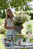Frau bringt Strauß aus Rosen und Sommerblumen zum gedeckten Tisch