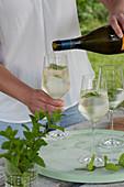 Frau füllt Gläser mit Prosecco, Strauß aus frischer Minze