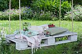 Weiße Palette als Sitzplatz mit Seilen an Baum gehängt, Krug mit Wasser, Minze und Himbeeren