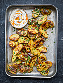 Roasted potatoes on baking tray with parsley and garlic