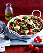 Schwarze Gemüsereis-Paella mit Tomaten und Artischocken